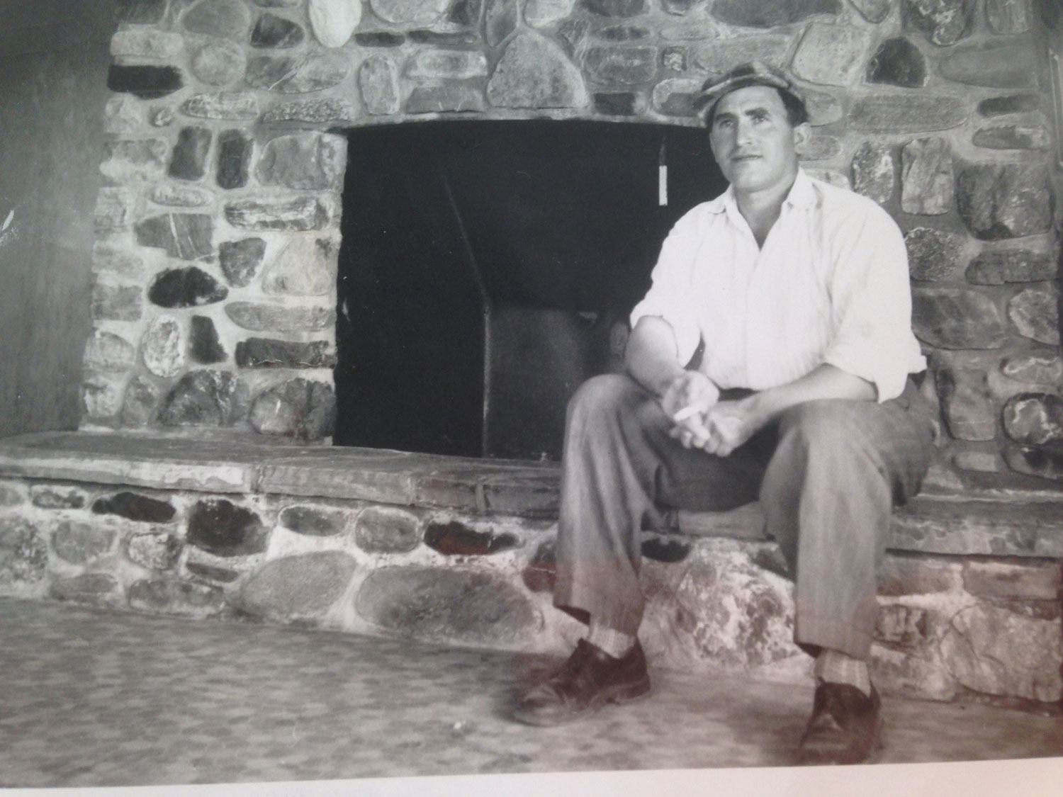 Max Helmer Sitting on Fireplace