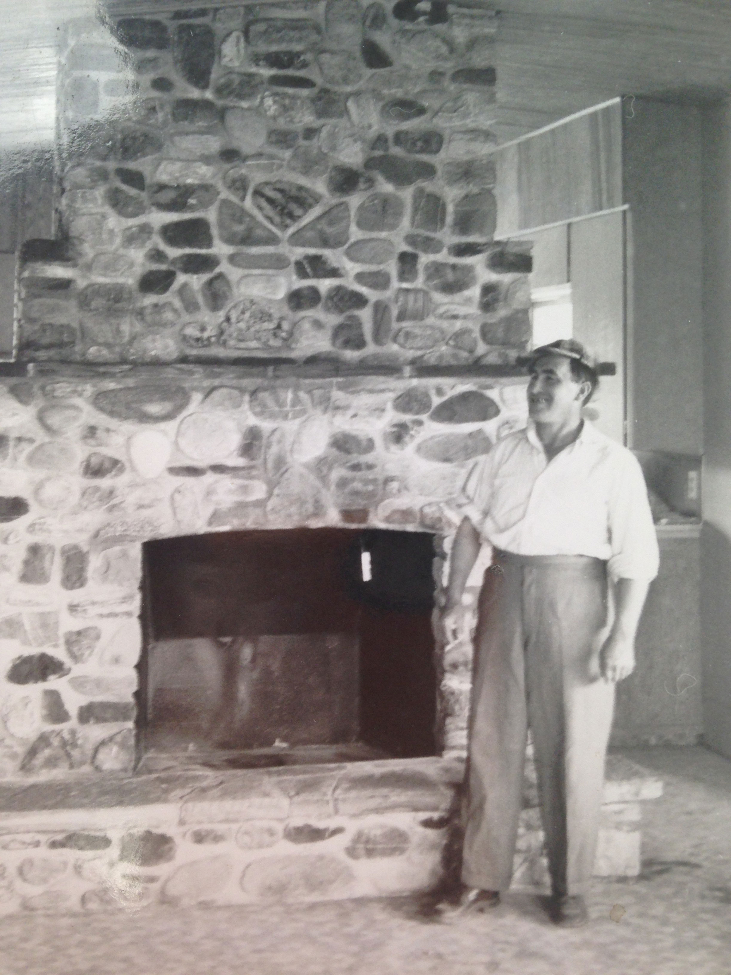 Max Helmer Standing by Fireplace